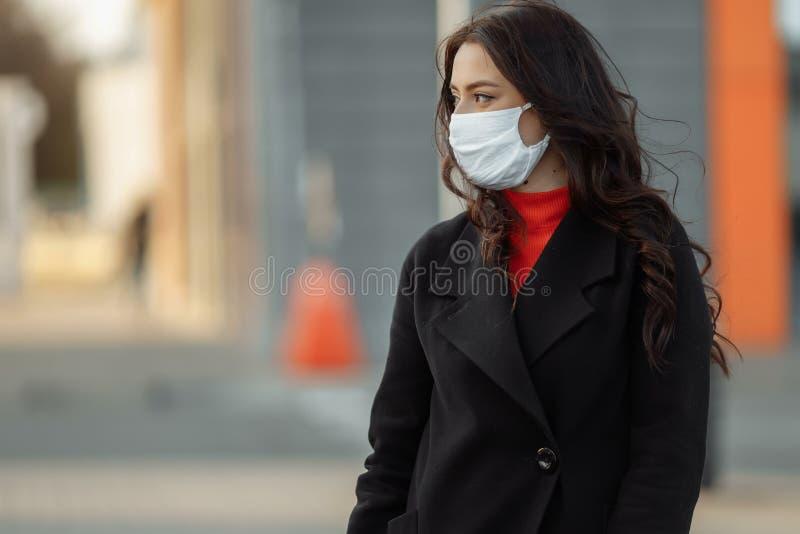 Strålningskänslig kvinna som går på gatan med skyddsmask som skydd mot smittsamma sjukdomar royaltyfria bilder
