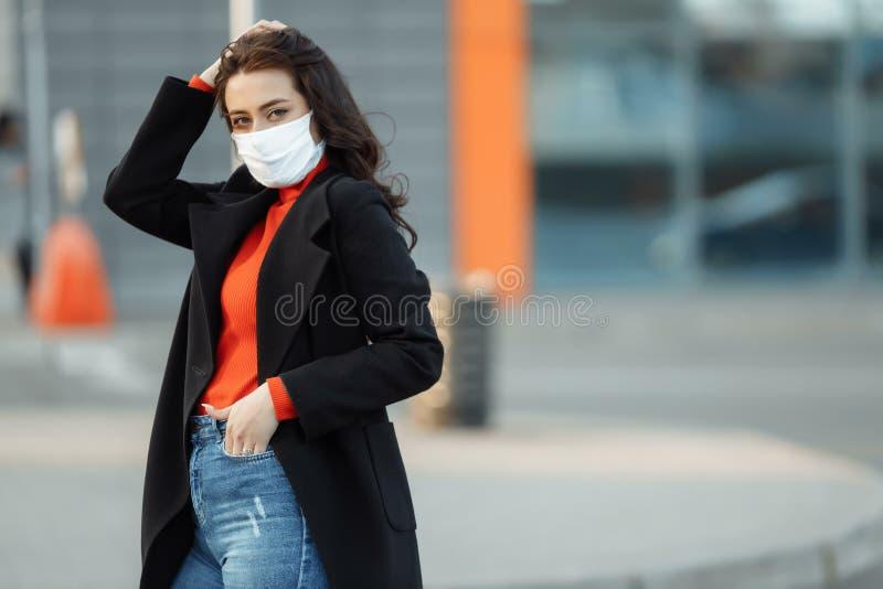 Strålningskänslig kvinna som går på gatan med skyddsmask som skydd mot smittsamma sjukdomar royaltyfri fotografi