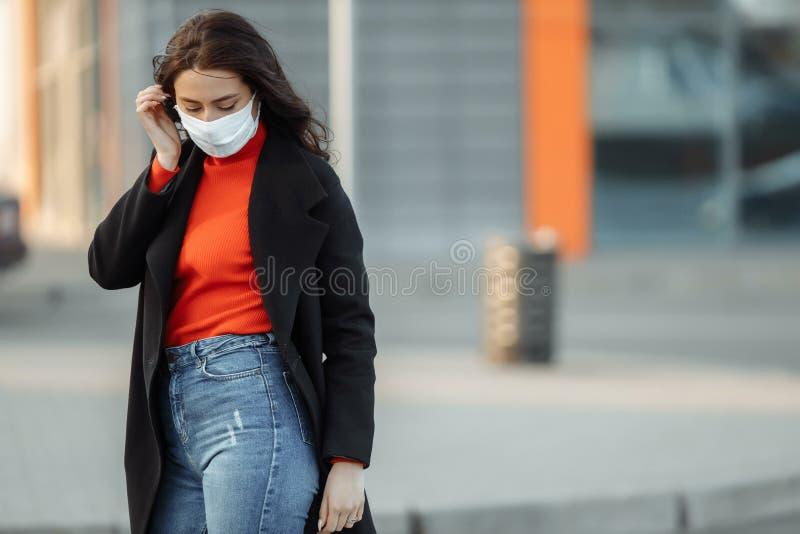 Strålningskänslig kvinna som går på gatan med skyddsmask som skydd mot smittsamma sjukdomar royaltyfri foto