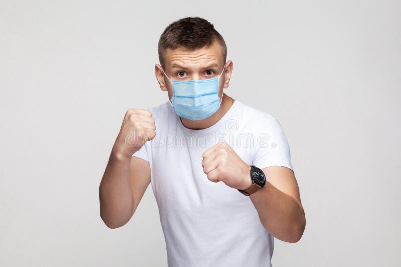 Strålningskänslig mot en ung man i vit skjorta med en kirurgisk mask som står med boxningsfister, som tittar på kameran och är re arkivfoto