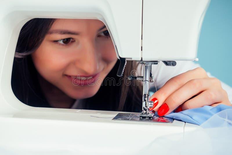 Strålningskänslig, porträttattraktiv kvinna, sömlös skräddarsydd smakertråd nålen på symaskinen på en blå arkivbilder