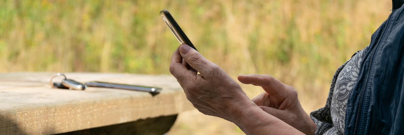 Strålningskänslig syn på höga kvinnliga händer med en smartphone royaltyfria bilder