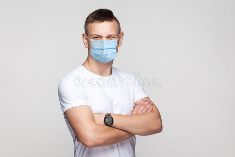 Strålningskänslig ung man i vit skjorta med kirurgisk medicinsk mask som står med övervapen och tittar på kamerans vinkling arkivbild