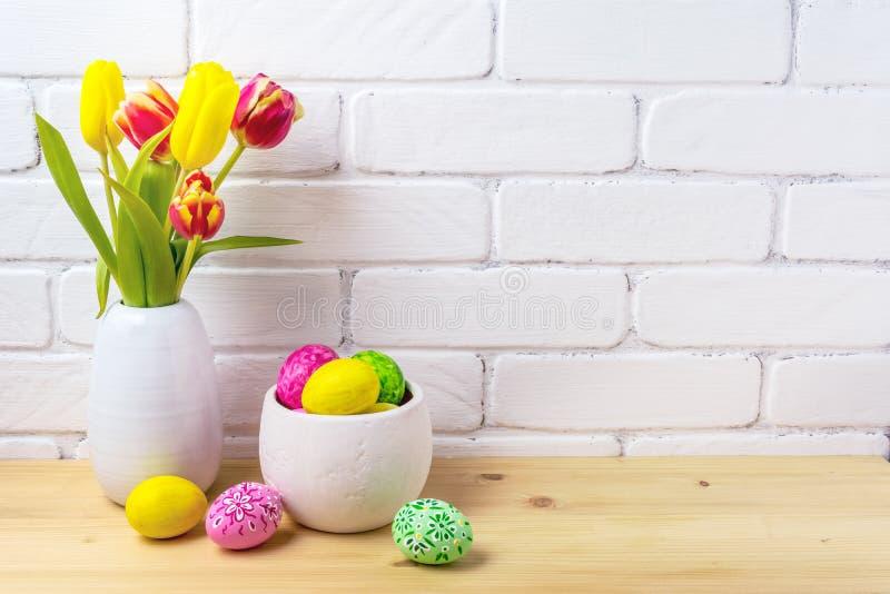 Strålningskänsliga arrangemang med ägg, röda och gula tulpaner royaltyfria foton