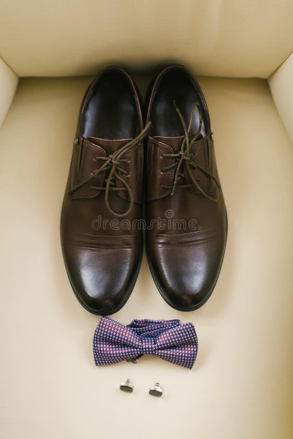 Strålningskänsliga skor av klassiska män med laces, trottoartid och koffslänkar på beige bakgrund arkivfoton