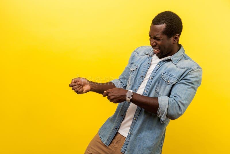 Strålningskanal av en ihärdig ung man som låtsas hålla rep i händerna och dra Inomhusstudio isolerad på gul bakgrund royaltyfri fotografi