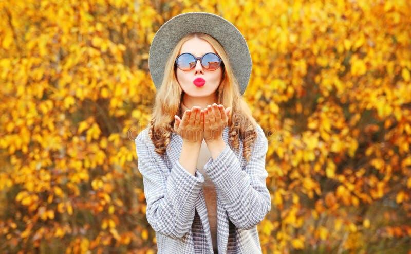 Strålningsknig kvinna på hösten som blåser röda läppar som skickar en söt luftkyss med grå rock, rund hatt på gula blad royaltyfria bilder