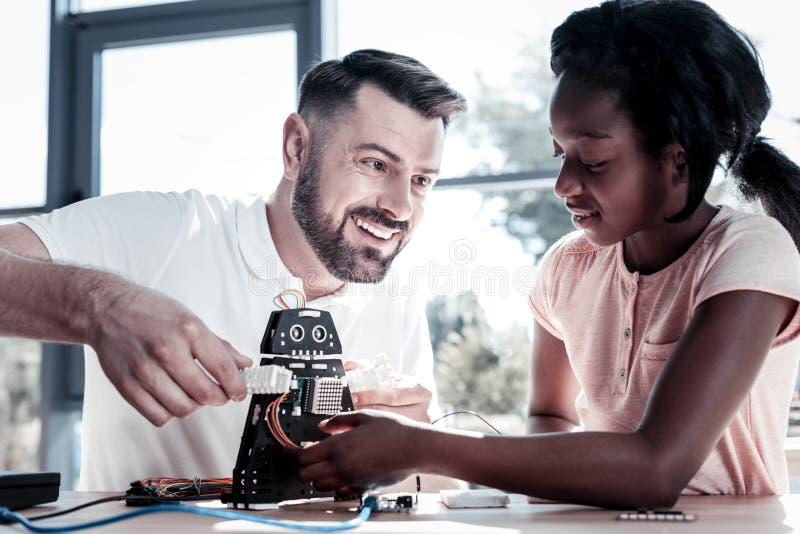 Strålningslärare som ler, medan arbeta med hans preteenstudent fotografering för bildbyråer