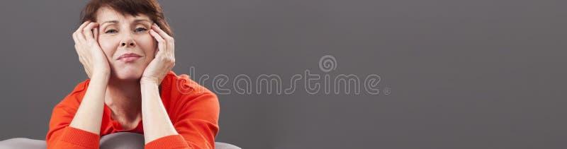 Strålningsmitt åldrades kvinnan som ler och kopplar av på säng, baner fotografering för bildbyråer