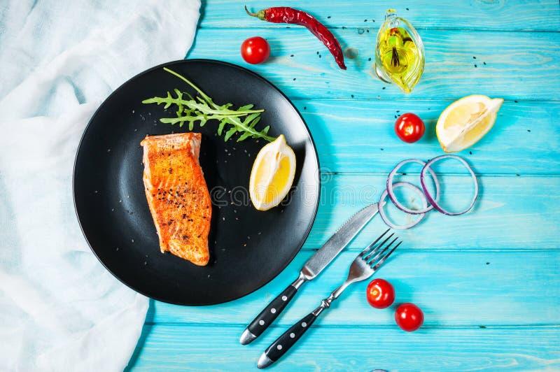 Strój jednoczęściowy piec łosoś z cytryną na czarnym talerzu Błękitny drewniany tło fotografia stock