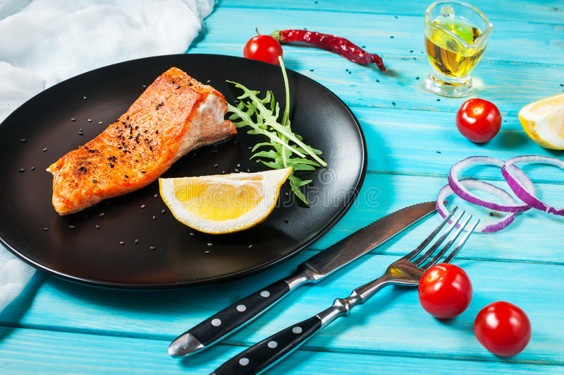 Strój jednoczęściowy piec łosoś z cytryną na czarnym talerzu Błękitny drewniany tło zdjęcia stock