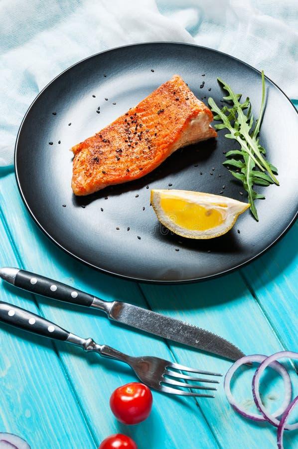 Strój jednoczęściowy piec łosoś z cytryną na czarnym talerzu Błękitny drewniany tło zdjęcie stock