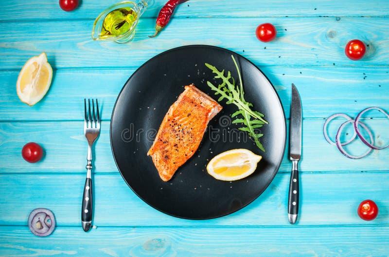 Strój jednoczęściowy piec łosoś z cytryną na czarnym talerzu Błękitny drewniany tło obrazy stock