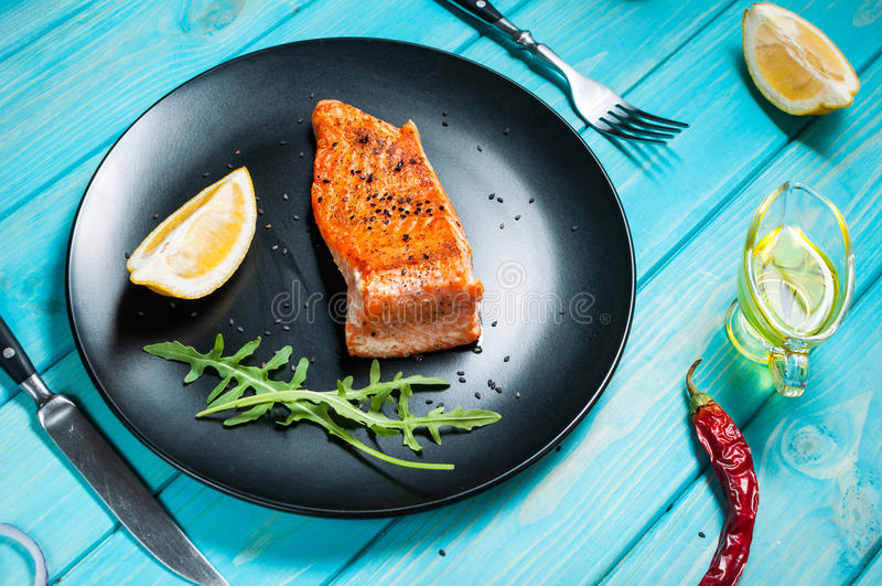 Strój jednoczęściowy piec łosoś z cytryną na czarnym talerzu Błękitny drewniany tło zdjęcia royalty free