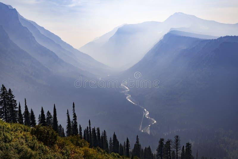 Ström till och med en dal för dimmigt berg i Montana royaltyfria bilder