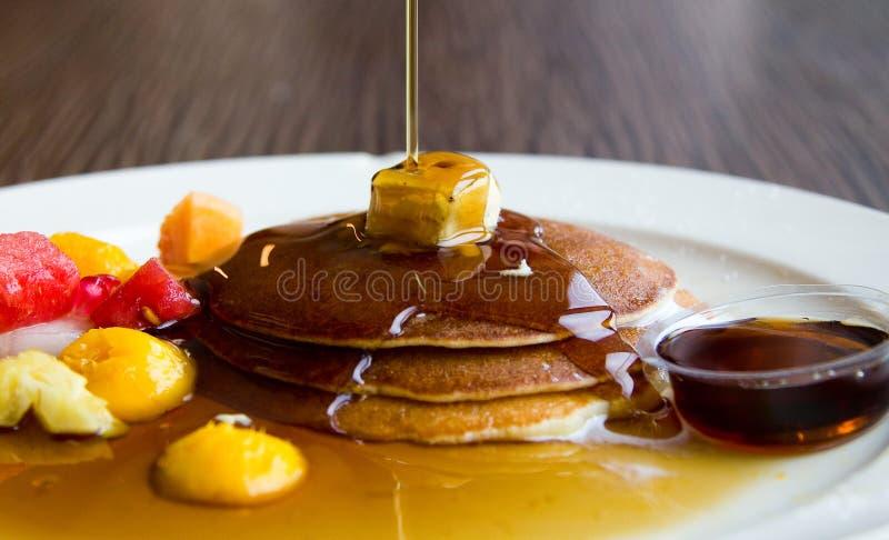 Strömender Ahornsirup auf drei Pfannkuchen mit Butter und Fruchtweißplatte lizenzfreies stockfoto