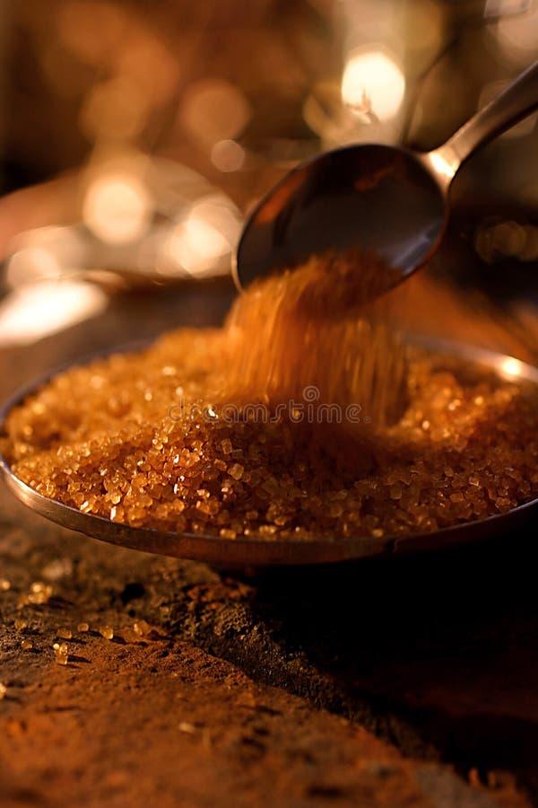Strömender brauner Zucker mit Löffel stockfotografie