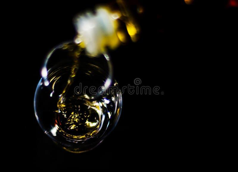 Strömender einzelner Malzwhisky in ein Glas, goldener Farbwhisky lizenzfreie stockfotos