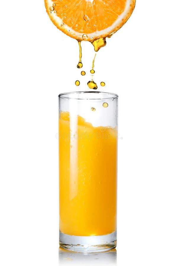 Strömender Orangensaft von der Orange in das Glas stockbilder