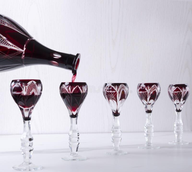 Strömender roter Alkohol in die Weinleseglaswaren, Buffetabendessen Konzept des Aperitifs lizenzfreies stockbild