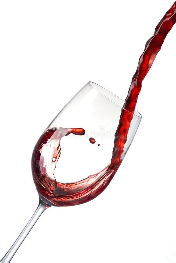 Strömender Rotwein in ein Kristallglas und stellt Wellen, spritzen her lizenzfreie stockfotos