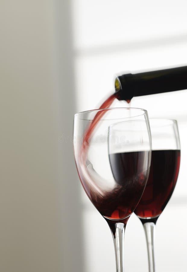 Strömender Rotwein in Glas lizenzfreies stockbild