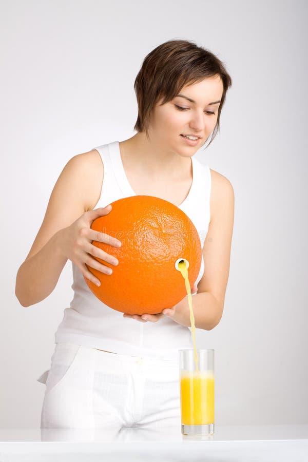 Strömender Saft des Mädchens von der riesigen Orange lizenzfreies stockbild