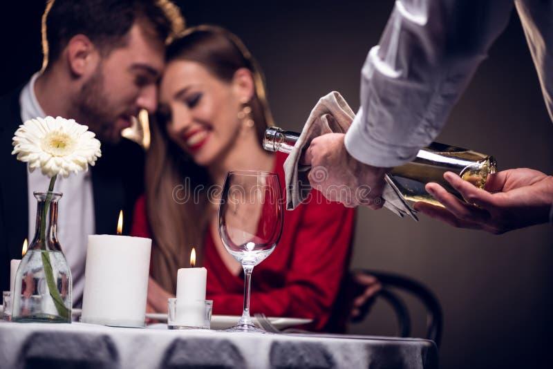strömender Wein des Kellners während schöne Paare, die romantisches Datum im Restaurant haben lizenzfreies stockbild