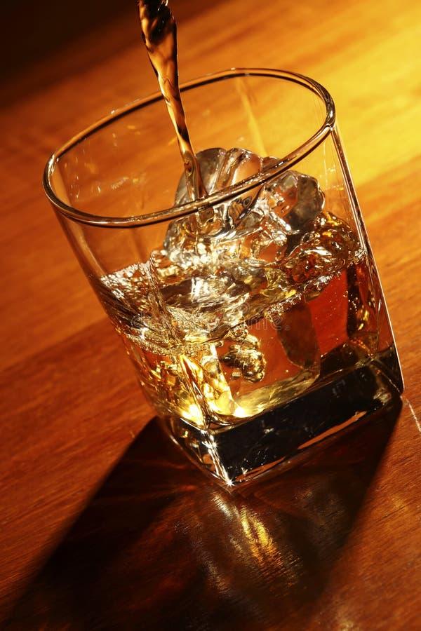 Strömender Whisky im Glas mit Eis lizenzfreie stockfotografie