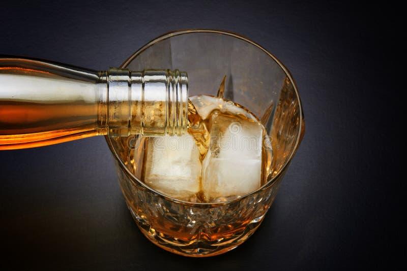 Strömender Whisky im netten Glas stockbild
