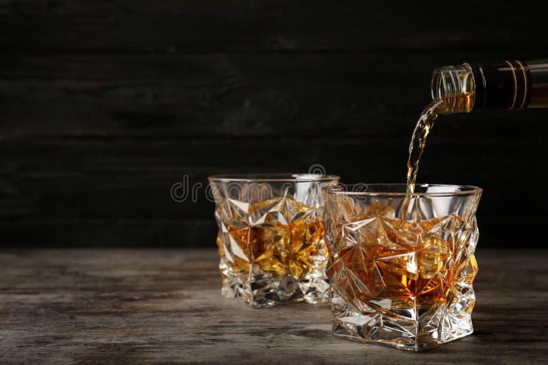 Strömender Whisky von der Flasche herein zum Glas mit Eiswürfeln auf Tabelle lizenzfreie stockfotografie