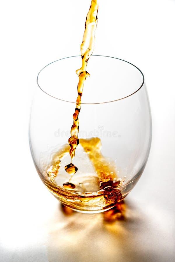 Strömender Whisky von der Flasche herein zum Glas ohne Eiswürfel auf weißer Tabelle lizenzfreie stockfotos