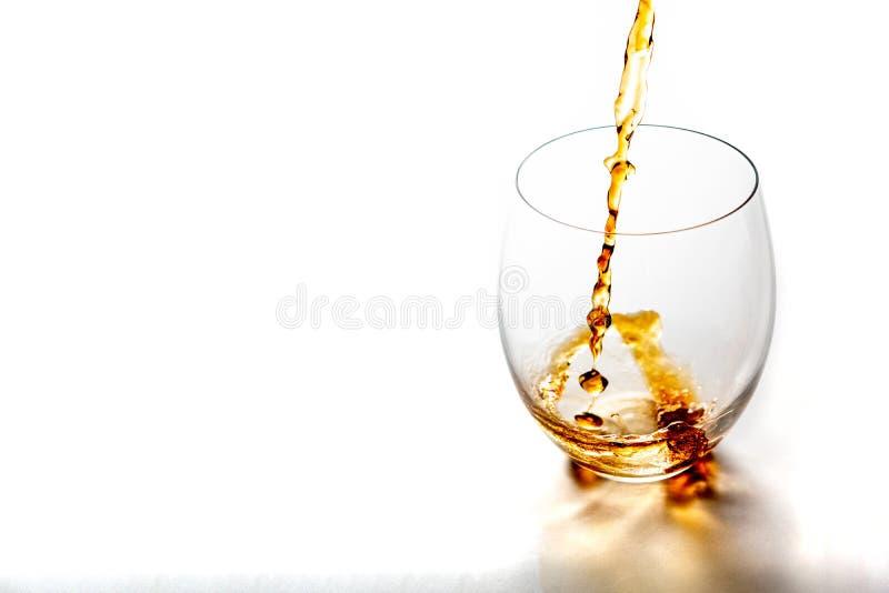 Strömender Whisky von der Flasche herein zum Glas ohne Eiswürfel auf weißer Tabelle stockfotografie
