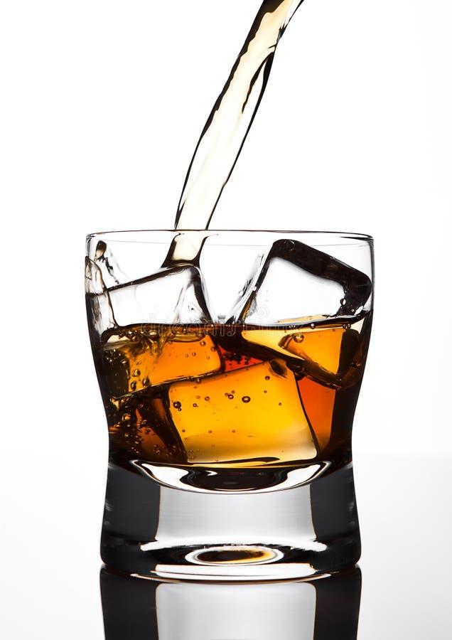 Strömender Whisky zum Glas mit Eiswürfeln lizenzfreie stockbilder