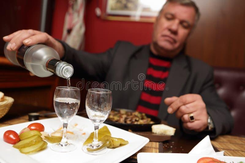 Strömender Wodka des älteren Mannes stockbilder