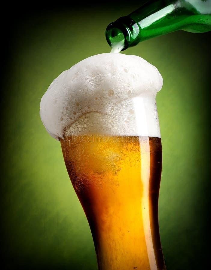 Strömendes Bier auf Grün stockfotos