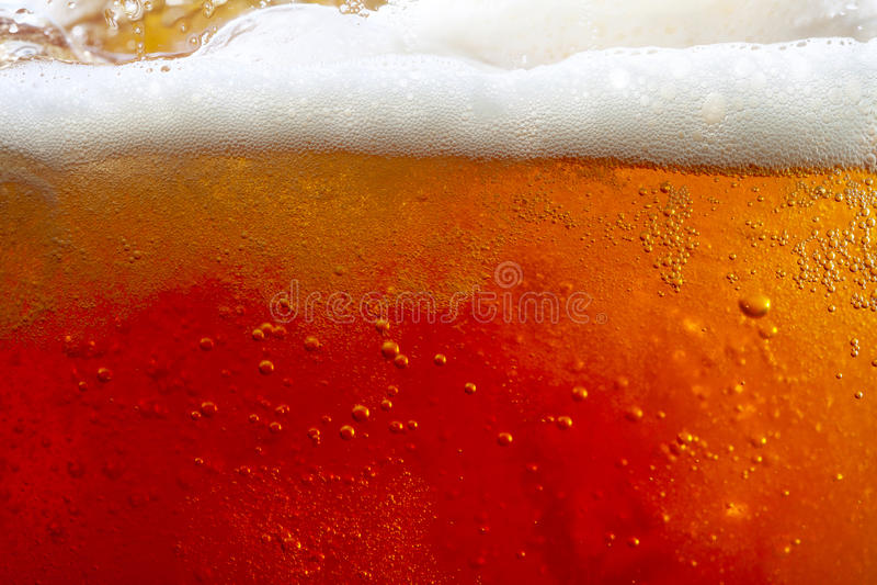 Strömendes Bier mit Luftblasen und Schaum stockfoto