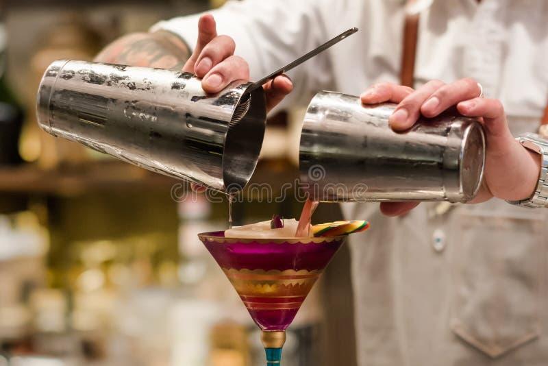 Strömendes Cocktail des Berufsbarmixers vom Schüttel-Apparat in das Glas Kellner, der im Handcocktailwerkzeug hält stockbild