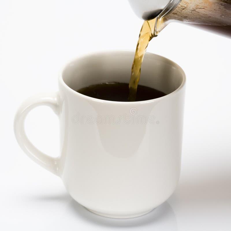 Strömendes coffe in Cup lizenzfreie stockfotos