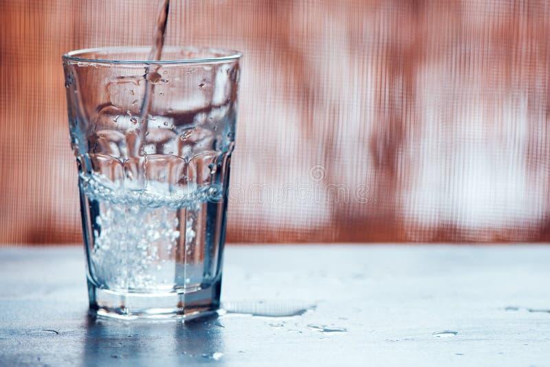 Strömendes sprudelndes Wasser in Trinkglas stockfotos