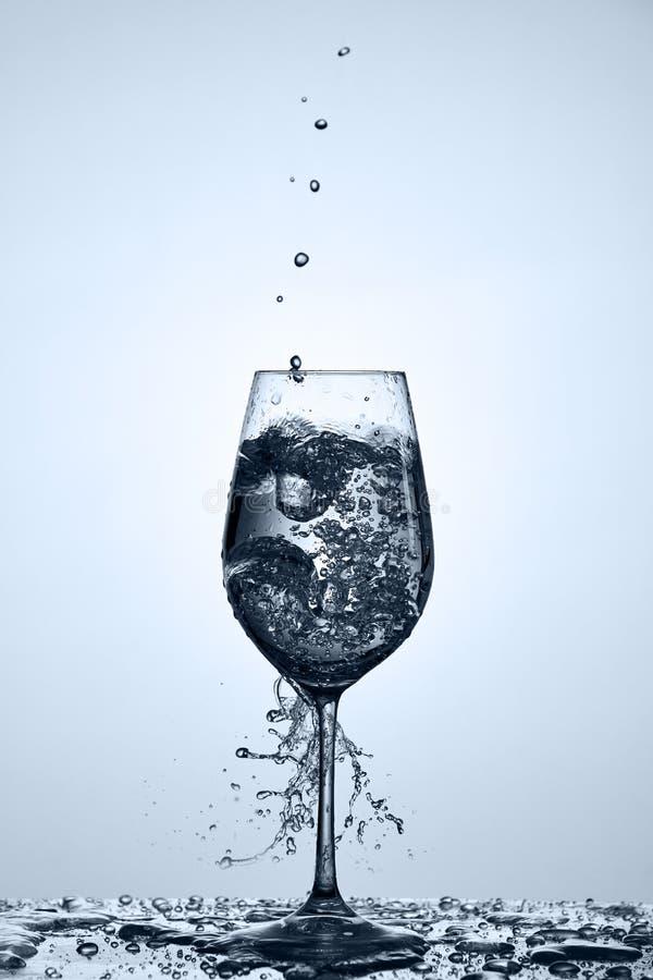 Strömendes transparentes Wasser in Weinglas mit schönem Wasser spritzt Stellung auf dem Glas gegen hellen Hintergrund stockfotografie