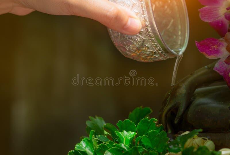 Strömendes Wasser der Nahaufnahmehandgriffwasser-Schüssel an Hand von Buddha-Statue für Wohlstand und Glück an Songkran-Tag Songk stockfotos