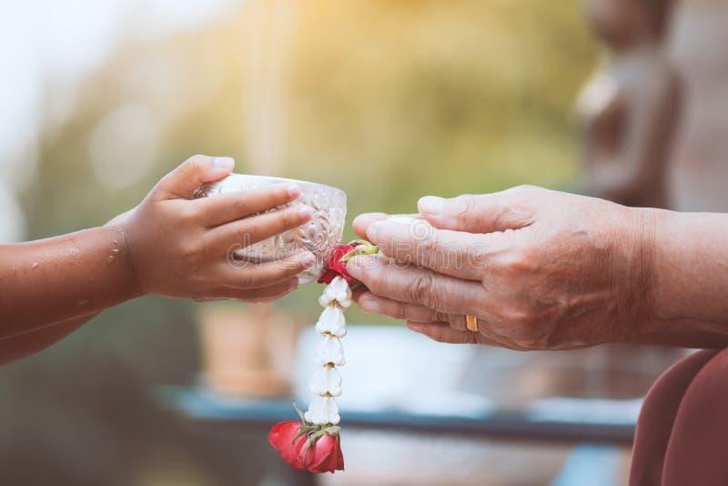 Strömendes Wasser des asiatischen kleines Kindermädchens auf Händen des älteren Seniors stockfotos