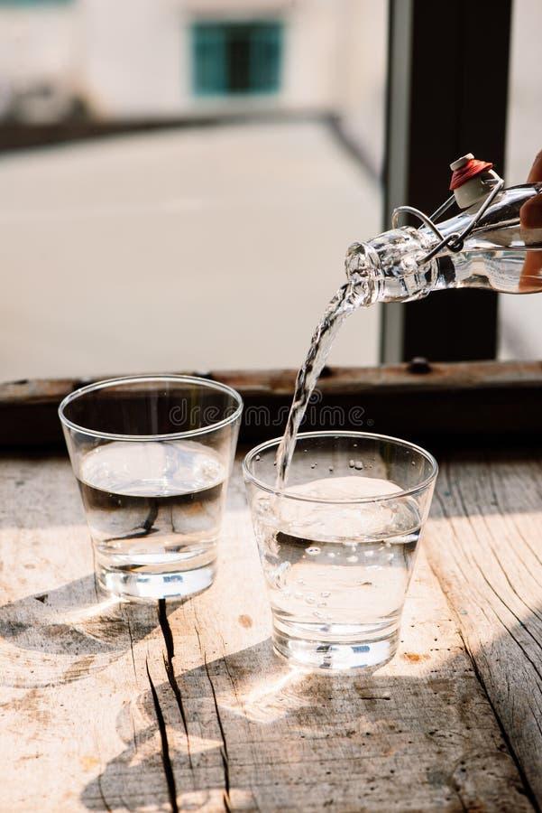 Strömendes Wasser in ein Glas stockbilder