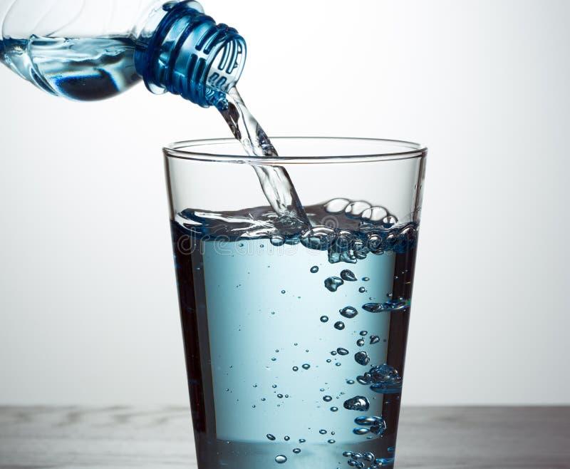 Strömendes Wasser von der Flasche in Glas lizenzfreie stockfotos