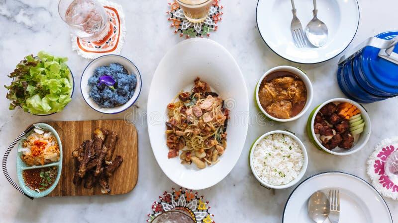 Strömma ris med persilja, Hang Lay Pork Curry och uppståndelse stekt griskött för extra- stöd med moroten och gurkan i matbärare royaltyfri foto