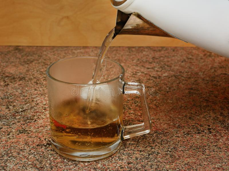 Strömmen av kokt vatten häller från den elektriska kokkärlet i ett exponeringsglas rånar ut med en tepåse arkivbilder