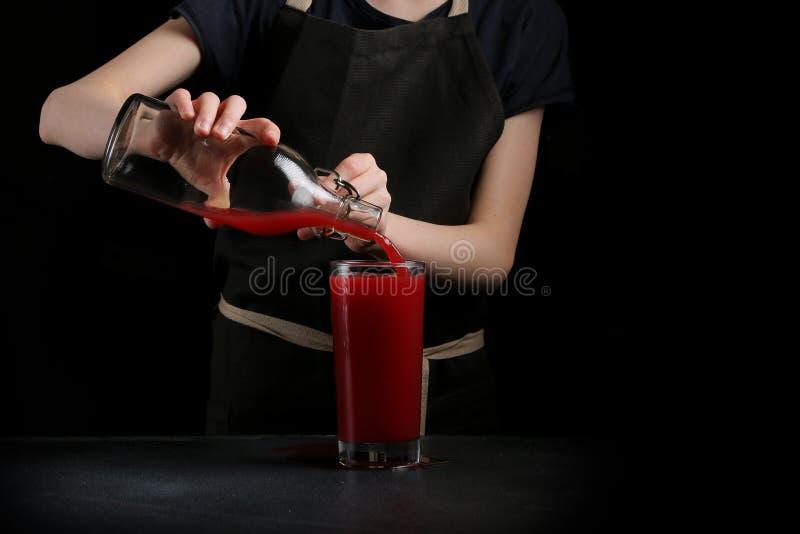 Str?mender Saft im Glas auf dunklem Hintergrund stockfoto