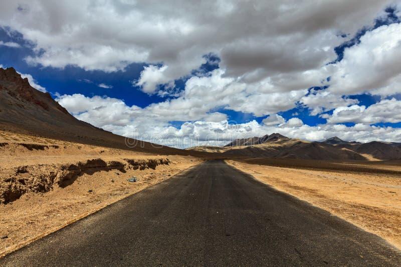 Straße auf Ebenen im Himalaja mit Bergen stockfotografie