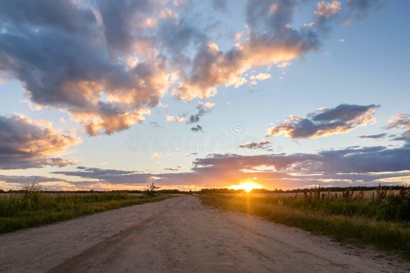 Straße auf einem Gebiet bei Sonnenuntergang mit Wolken stockfotografie